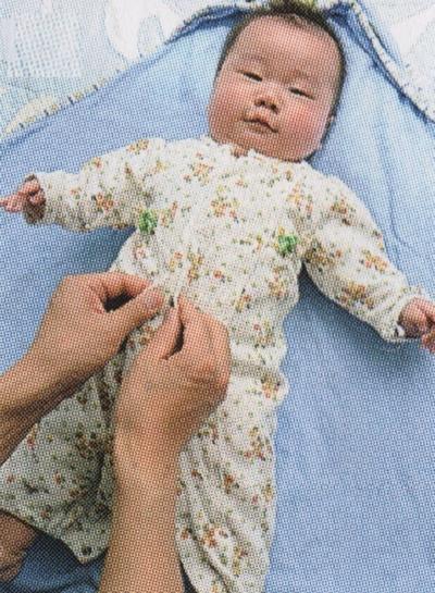 赤ちゃんの服を着せる