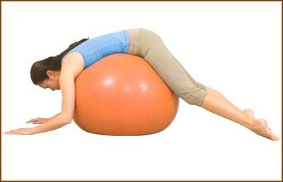 バランスボールに乗って背中を伸ばす